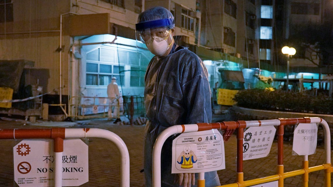 A personnel wearing protective suit waits near an entrance at the Cheung Hong Estate, a public housing estate during evacuation of residents in Hong Kong, Tuesday, Feb. 11, 2020. (AP)