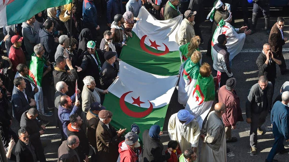 Algerians carry large national flags as they march in an anti-government demonstration in the capital Algiers on February 14, 2020. (AFP)