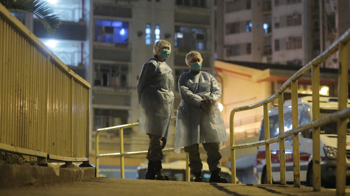 People wearing protective suits stand near the Cheung Hong Estate, a public housing estate, during evacuation of residents in Hong Kong, Tuesday, Feb. 11, 2020. (AP)
