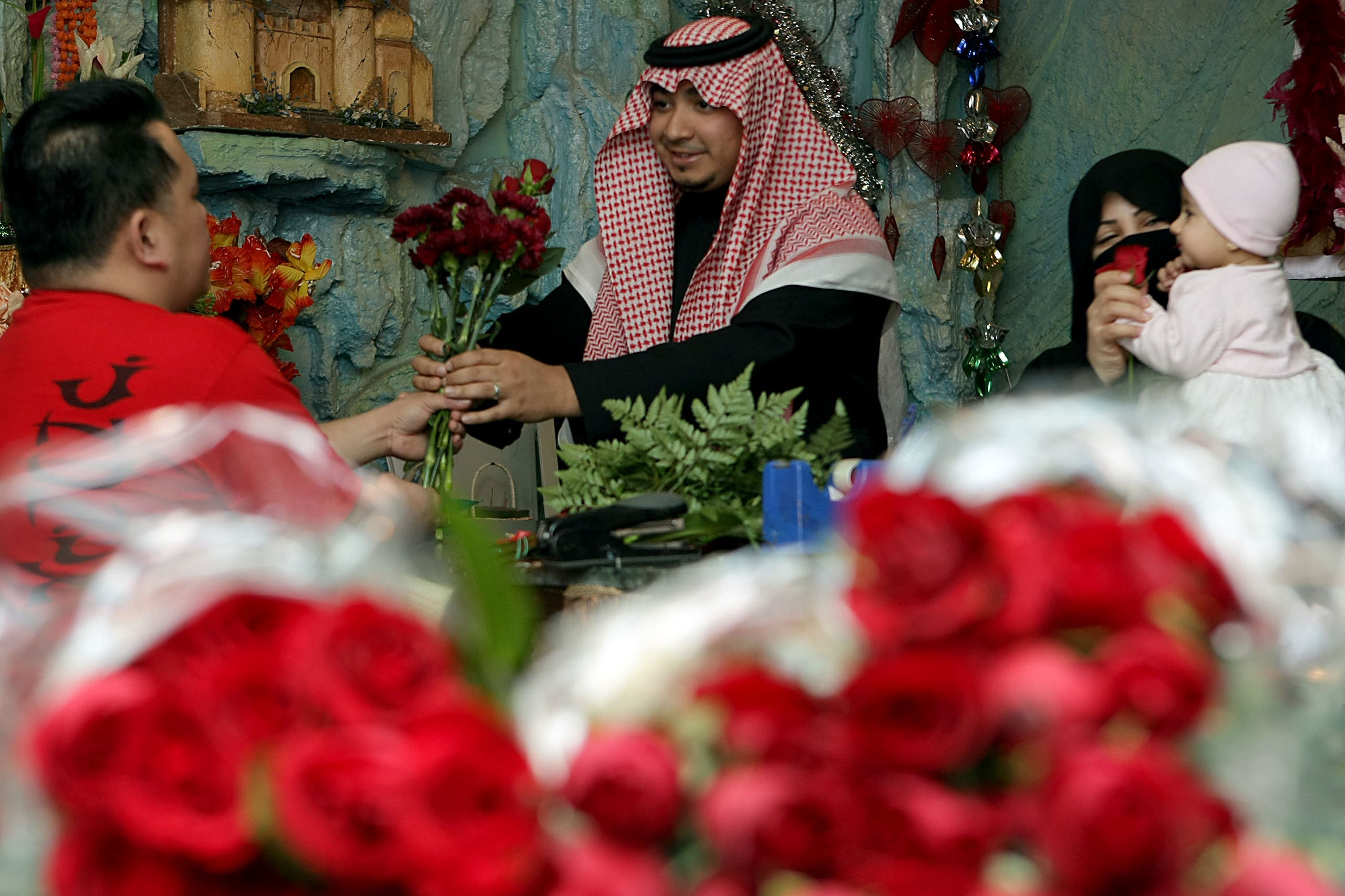 A Saudi man buys red roses for his wife at a flower shop in Riyadh on the eve of Valentine's Day on February 13, 2009. (AFP)