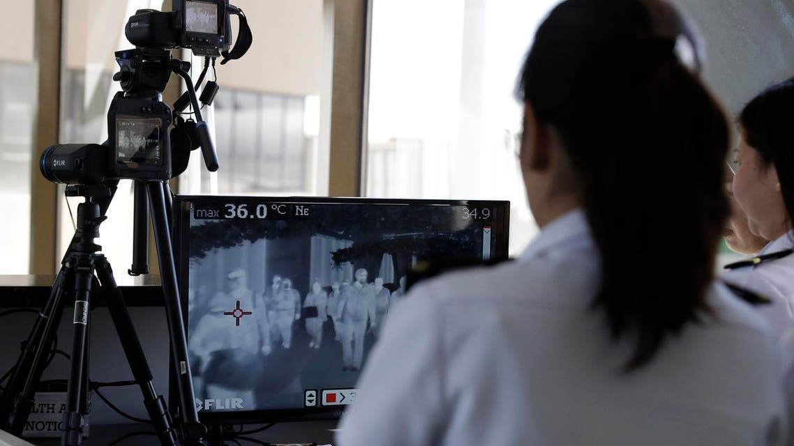 Airport personnel look at thermal scanners as they check on arriving passengers at Manila's international airport, Philippines, Thursday, Jan. 23, 2020.(AP)