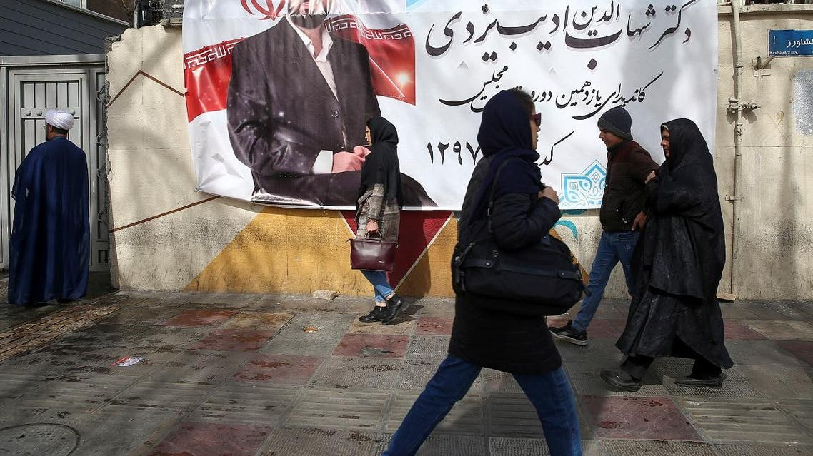 People walk past a parliamentary election campaign poster in Tehran, Iran February 15, 2020. (Reuters)