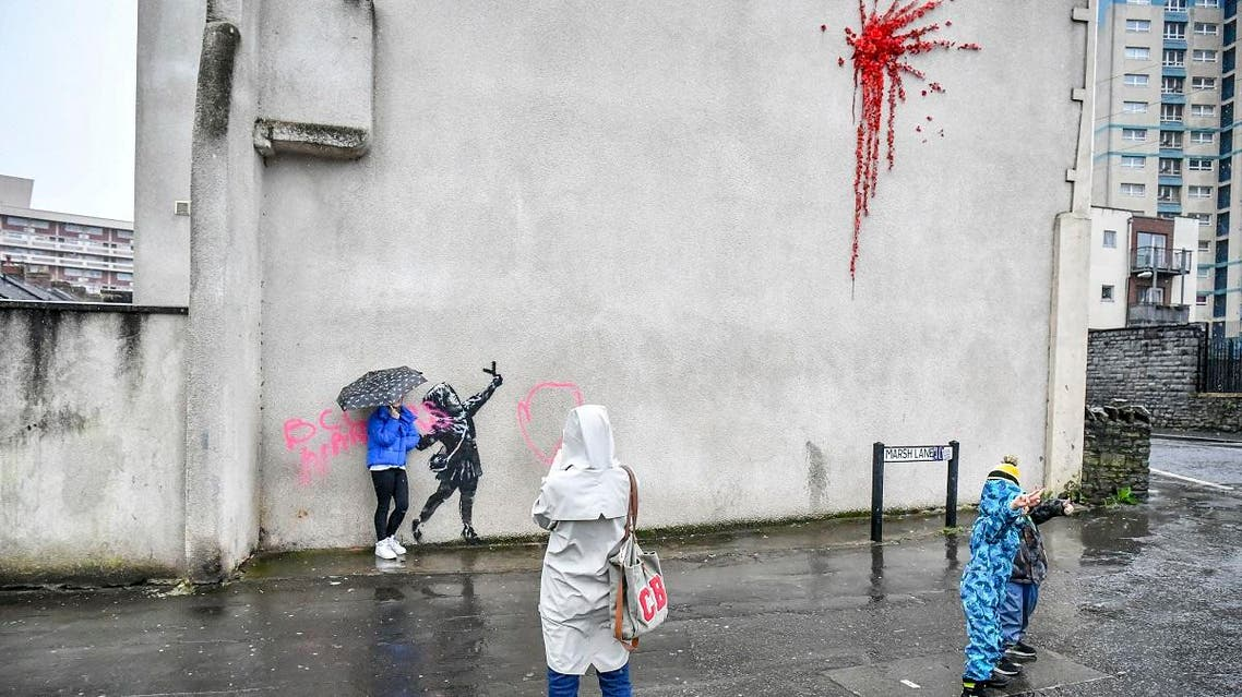People take photos of a mural by Bansky which has been vandalised, on the side of a house on Marsh Lane, in Barton Hill, Bristol, England, Saturday, Feb. 15, 2020. (AFP)