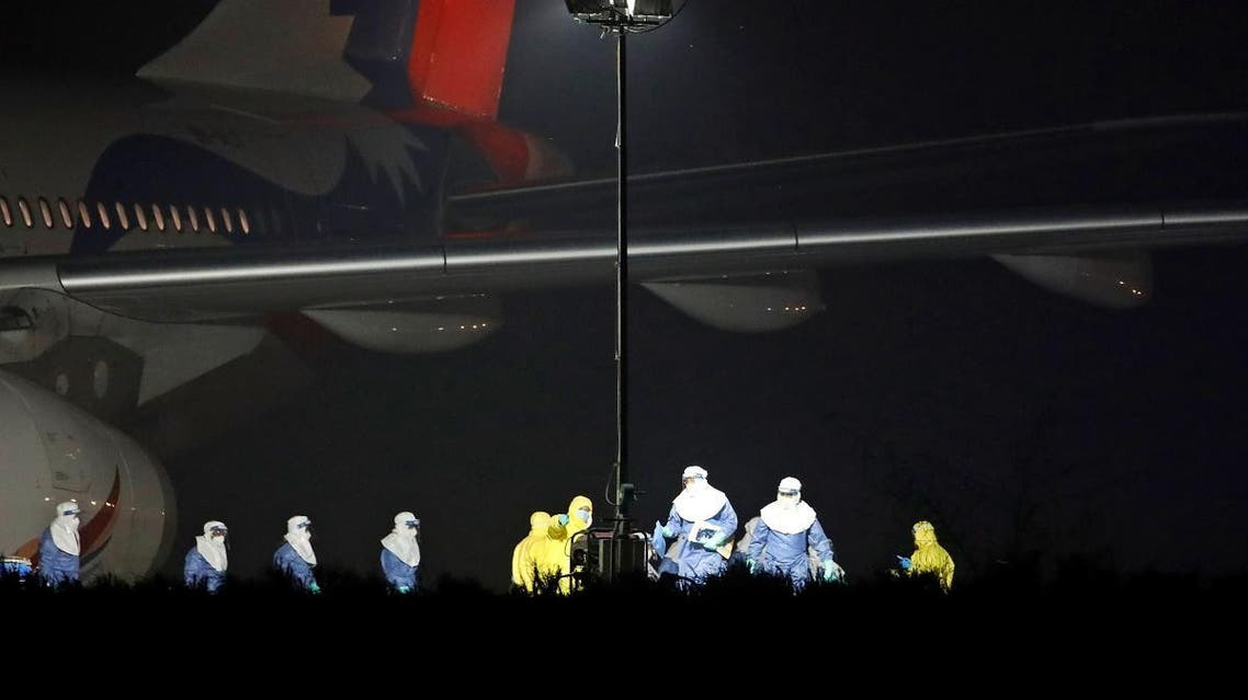 Officials in protective suites prepare to evacuate 175 Nepalese nationals from a Nepal Airlines plane arriving from coronavirus-stricken Chinese city of Wuhan. (Photo: Reuters)