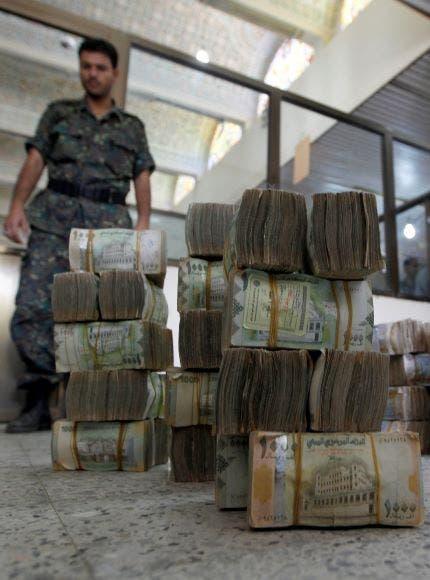 عنصر حوثي وأمامه رزم من العملة الوطنية (فرانس برس - أرشيفية)