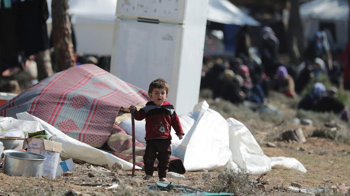 An internally displaced child walks at a makeshift camp in Qatmah village, West of Azaz. (Reuters)