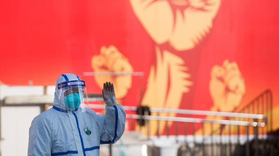 A medical worker waves near a propaganda poster as patients arrive at a temporary hospital with 1100 beds converted from the Wuhan Sports Center. (AP)