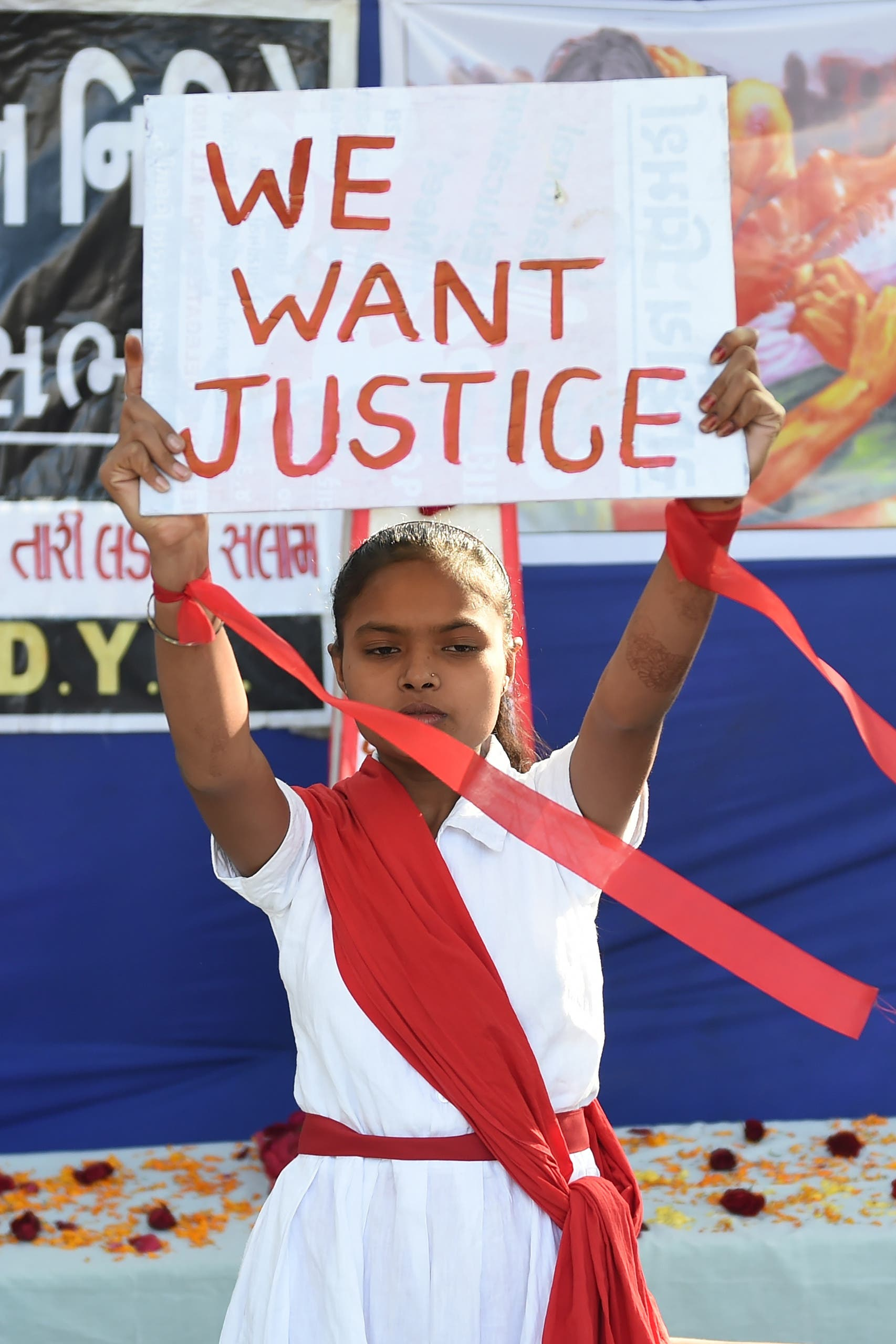 A young student holds a placard during 'Nirbhaya Day' to mark the anniversary of the brutal rape case of a 23-year-old physiotherapy student on a bus in New Delhi in 2012, in Ahmedabad on December 16, 2019.