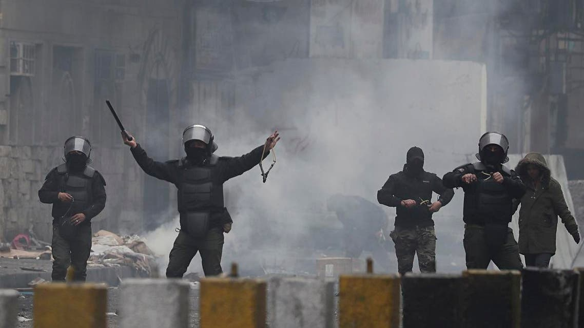 Security forces prepare to use slingshots to disperse anti-government protesters during clashes in central Baghdad, Iraq. (AP)