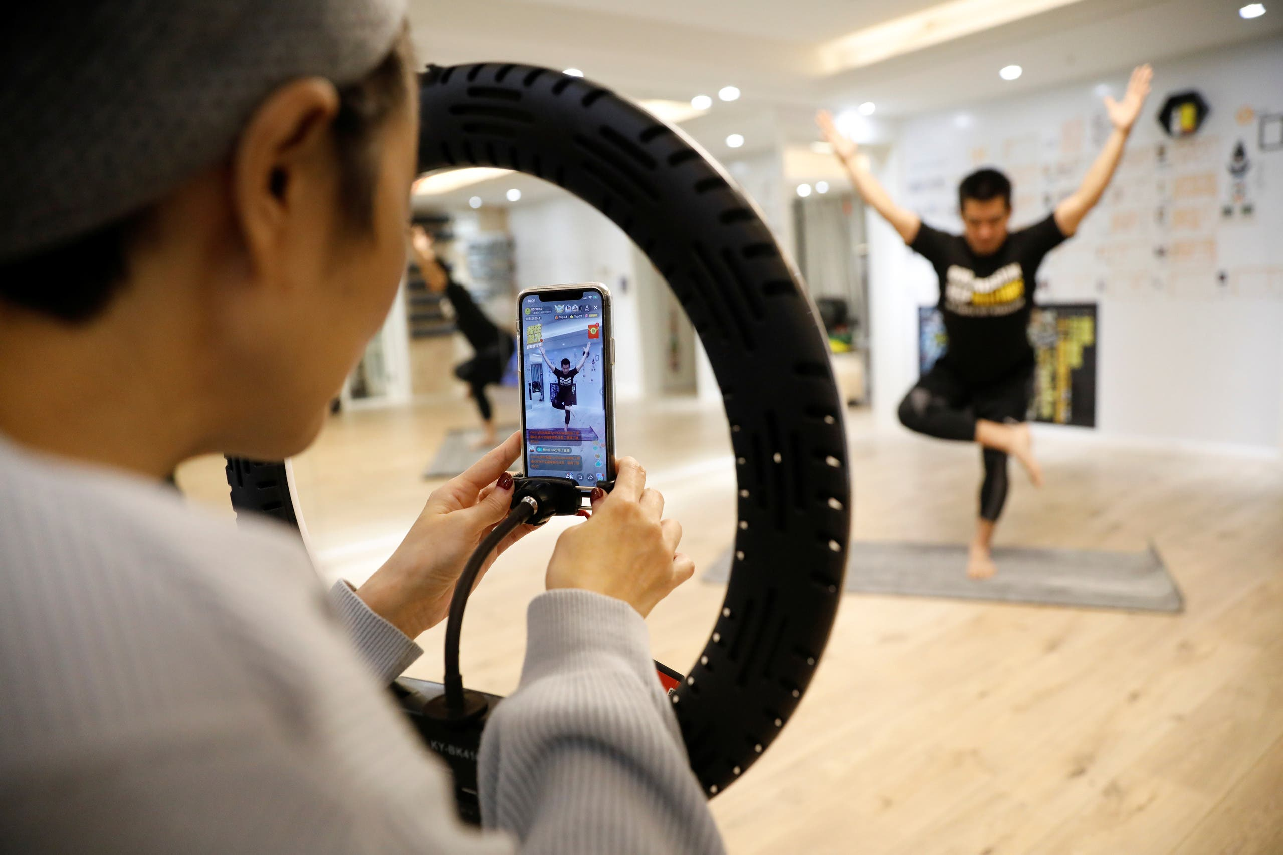 Liu Xiaojin, sets a phone as she gets ready to livestream a gym class, as the country is hit by an outbreak of the new coronavirus, in Beijing. (Reuters)