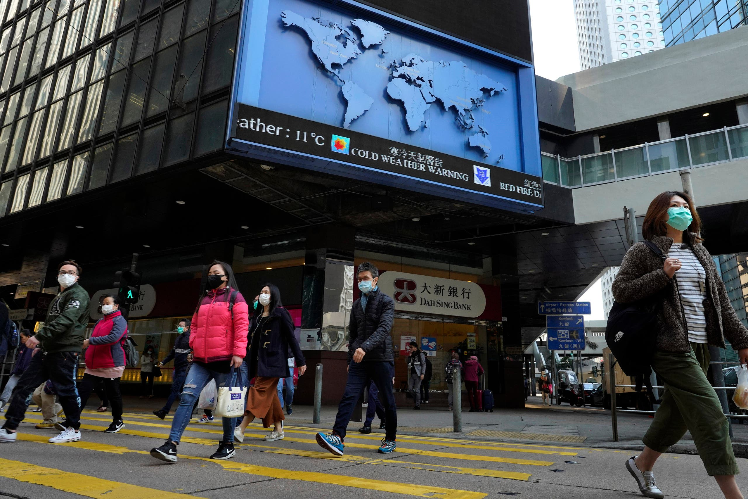 People wearing face mask walk at a downtown street in Hong Kong. (AP)