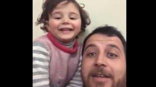"""مشهد مؤثر.. أب سوري """"مطمئناً"""" ابنته: القذائف لعبة"""