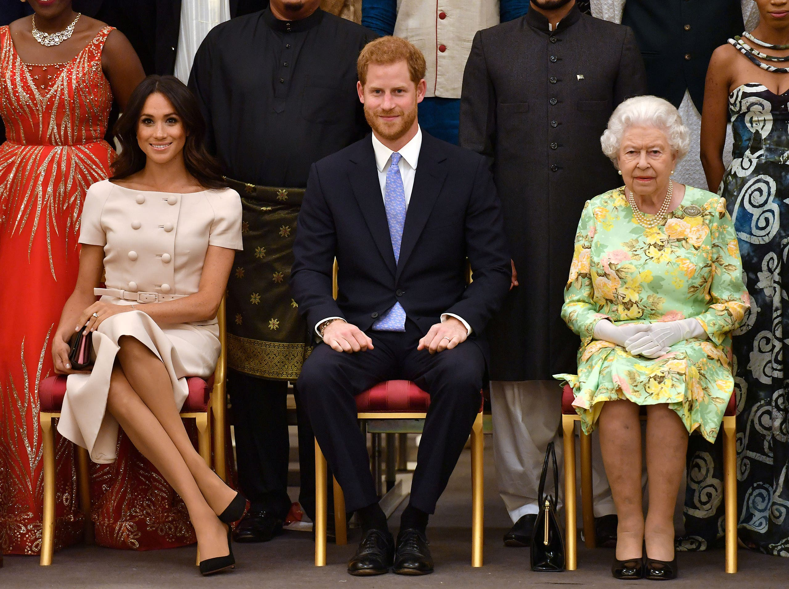 Britain's Queen Elizabeth, Prince Harry and Meghan, the Duchess of Sussex pose for a picture with some of Queen's Young Leaders at a Buckingham Palace reception in London on June 26, 2018. (Reuters)