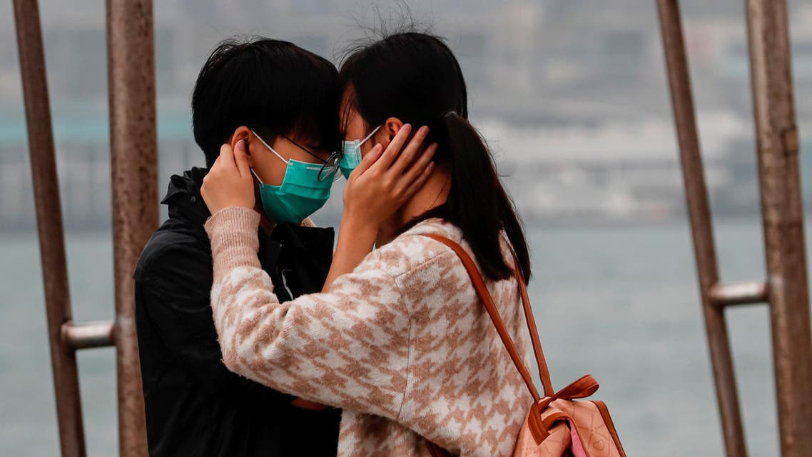 A couple wears masks as the embrace, following the outbreak of the novel coronavirus on Valentine's Day in Hong Kong. (Reuters)
