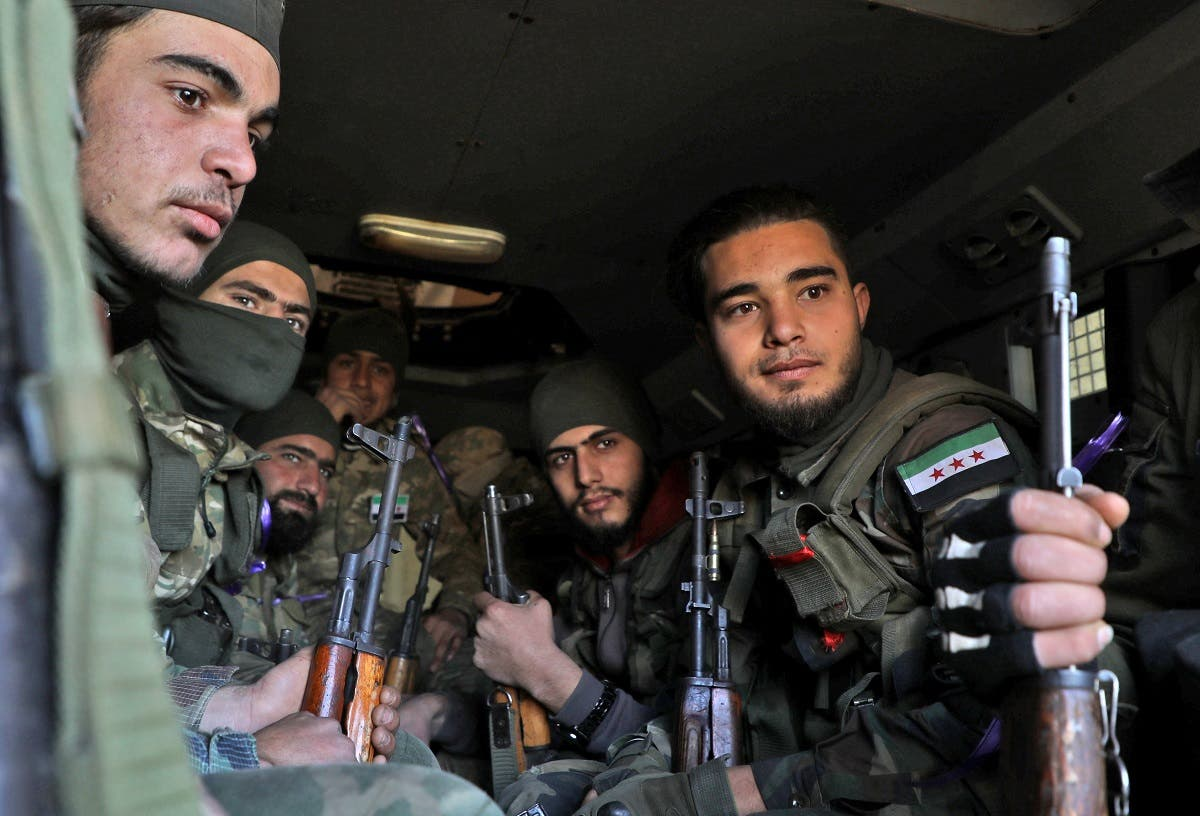 Turkish-backed Syrian fighters sit together inside a vehicle in the town of Qaminas in the southern countryside of the northwestern Idlib province on February 20, 2020, as they prepare to head into combat against government forces in nearby Nayrab to the southeast. (AFP)
