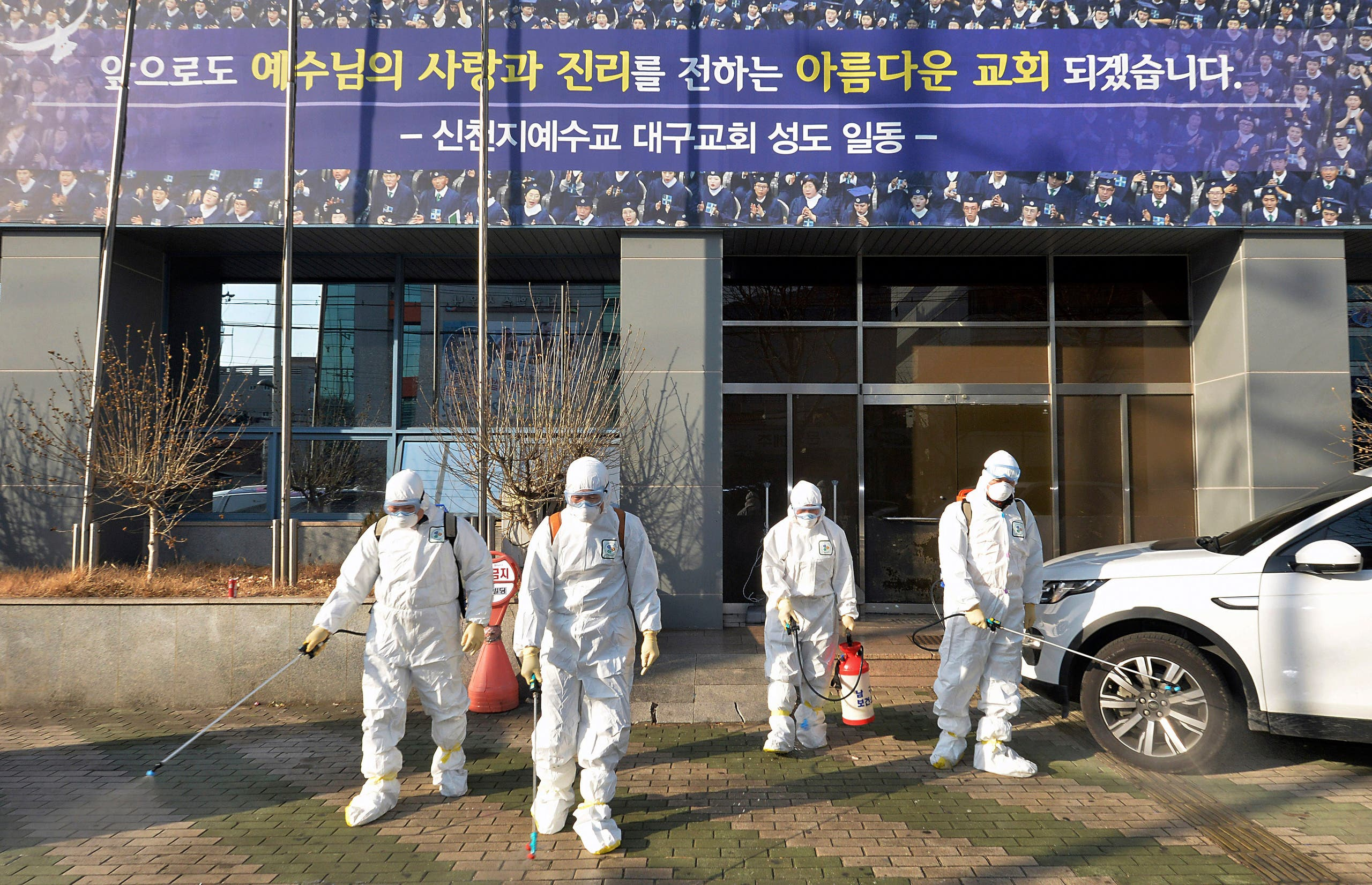 In this Wednesday, Feb. 19, 2020, photo, workers wearing protective gears spray disinfectant against the coronavirus in front of a church in Daegu, South Korea. - AP