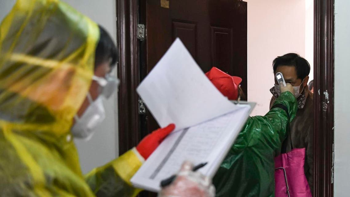 Workers go door to door to check the temperature of residents during a health screening campaign in the Qingheju Community, Qingshan District of Wuhan in central China's Hubei Province. (AP)
