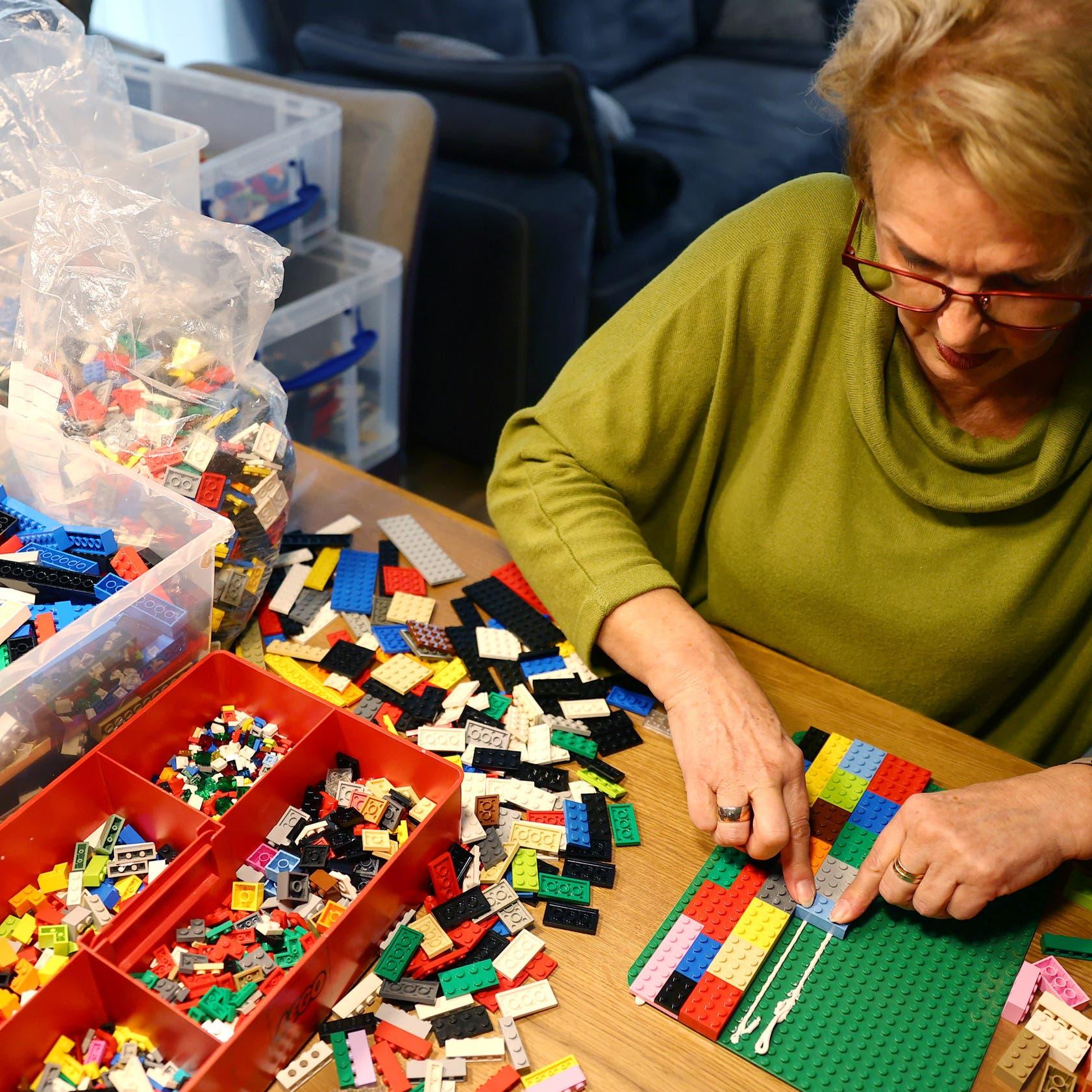 """بالصور.. جدة مقعدة تساعد ذوي الإعاقة بقطع """"الليغو"""""""