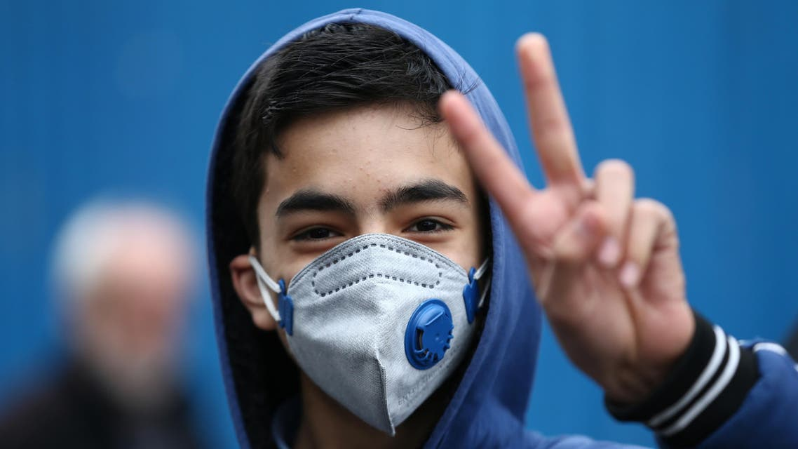 An Iranian boy gestures as he wears protective mask to prevent contracting a coronavirus in Tehran. (Reuters)