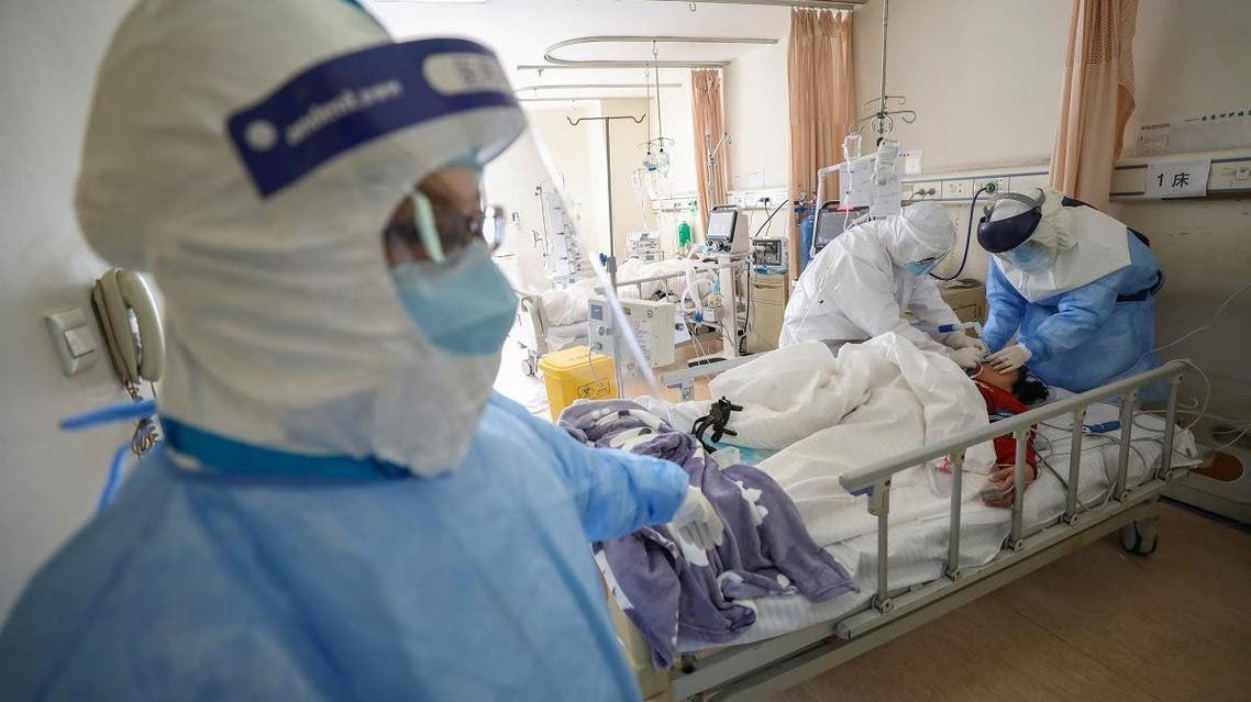 Medical workers in protective suits attend to a patient inside an isolated ward of Wuhan Red Cross Hospital in Wuhan. (Reuters)