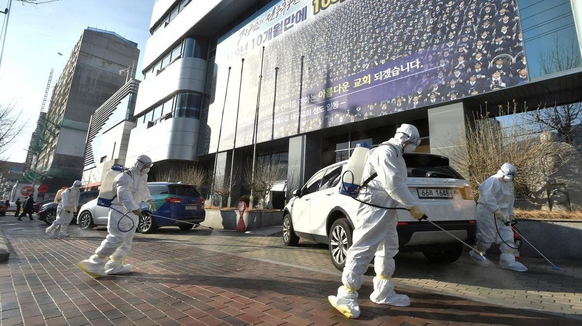"Workers from a disinfection service company sanitize a street in front of a branch of the Shincheonji Church of Jesus the Temple of the Tabernacle of the Testimony where a woman known as ""Patient 31"" attended a service in Daegu, South Korea, February 19, 2020. Yonhap via REUTERS"