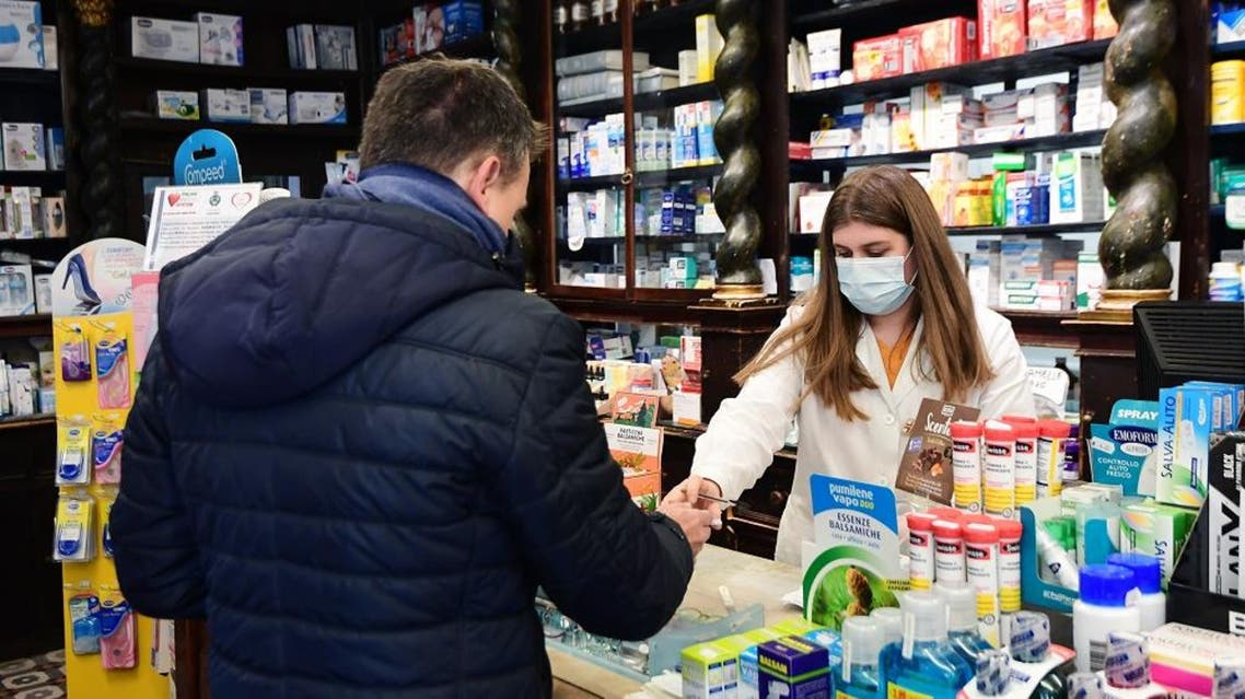 A pharmacist wearing a protective respiratory mask tends to a customer in Codogno, southeast of Milan, on February 22, 2020. afp