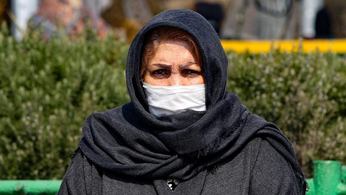 An Iranian woman wearing a protective mask and gloves, stands in a busy street in the capital Tehran on February 22, 2020. (AFP)