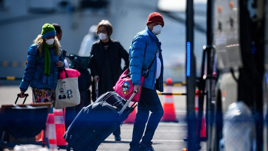 Mask-clad passengers prepare to board a bus after disembarking from the Diamond Princess cruise ship, in quarantine due to fears of new COVID-19 coronavirus, at Daikoku pier cruise terminal in Yokohama on February 21, 2020. (AFP)