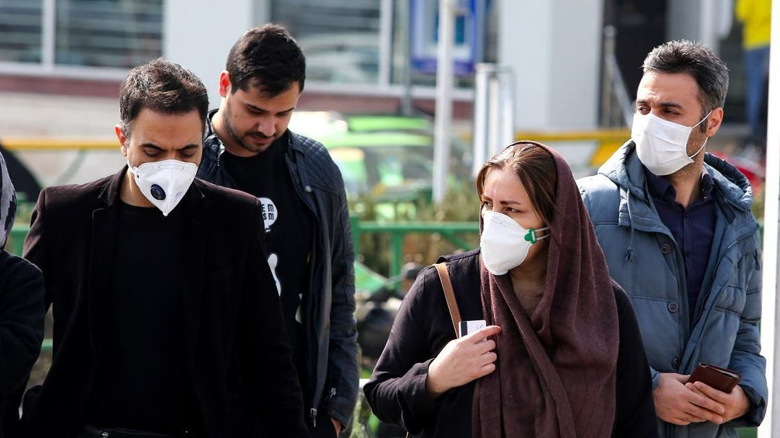 Iranians, some wearing protective masks, wait to cross a street in the capital Tehran on February 22, 2020. (AFP)