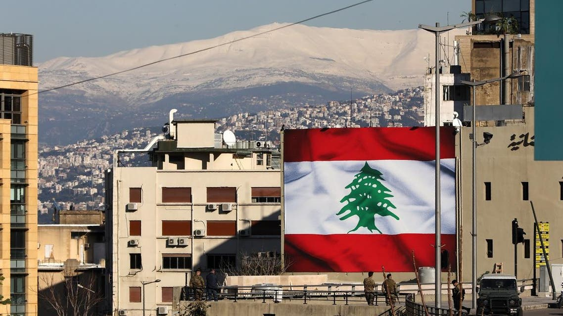 A picture taken on January 25, 2020, shows Lebanese soldiers standing guard beneath a giant national flag in the capital Beirut. (AFP)