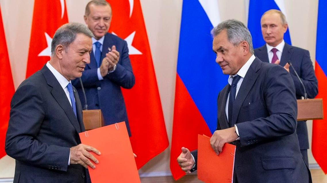 Russian Defense Minister Sergei Shoigu (frontR) exchanges documents with Turkish Defense Minister Hulusi Akar (frontL). afp