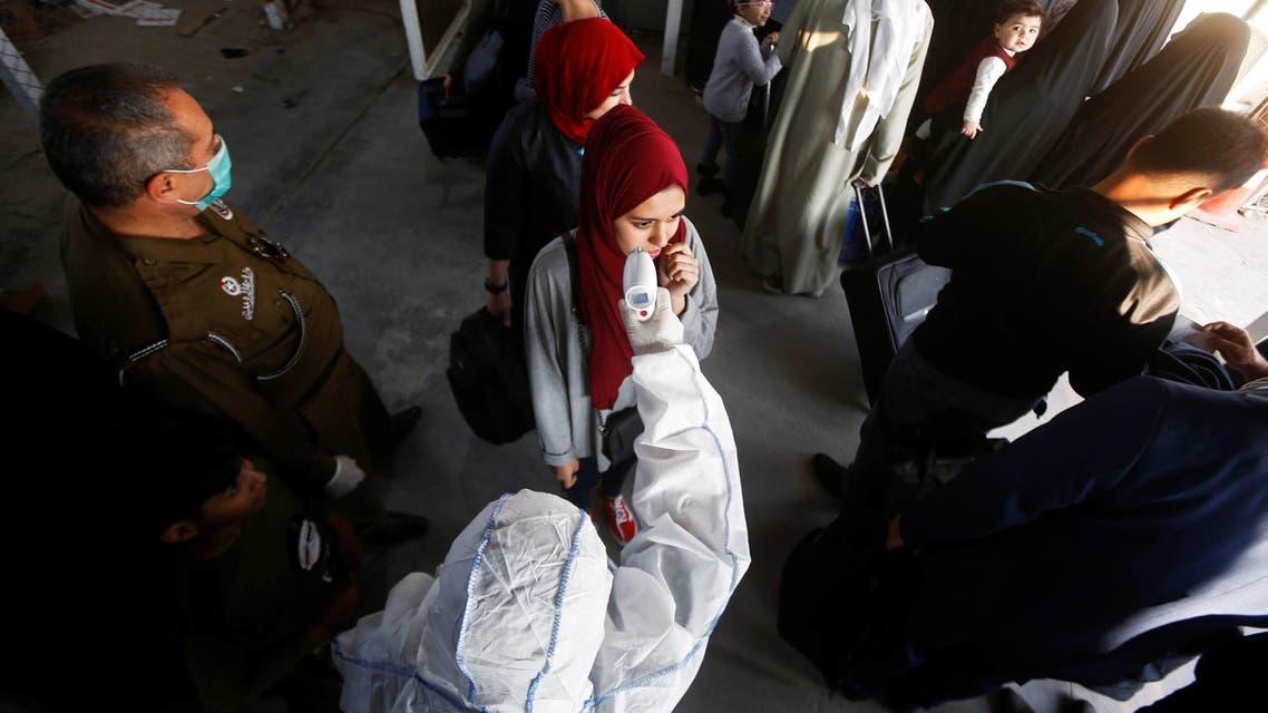 An Iraqi medical staff member checks a passenger's temperature, amid the new coronavirus outbreak, upon her arrival to Shalamcha Border Crossing. (Reuters)