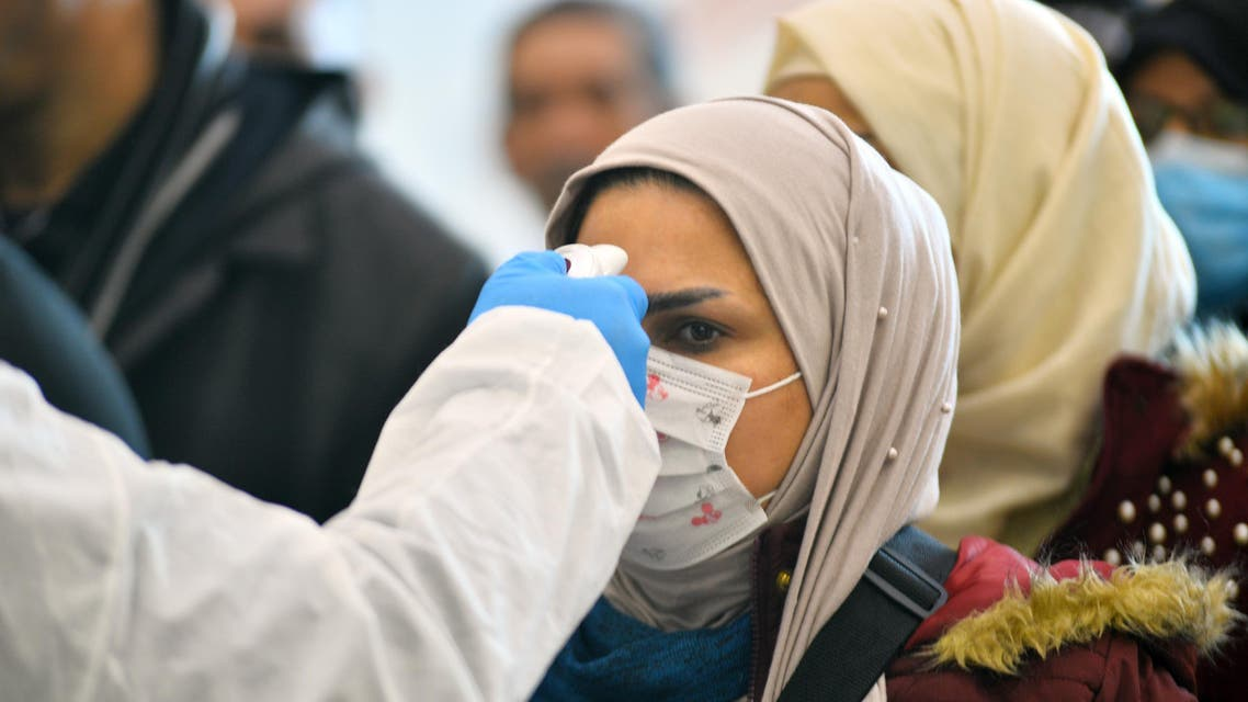 The body temperature of an Iraqi woman returning from Iran is measured upon her arrival at the Najaf International Airport on February 21, 2020, after Iran announced cases of coronavirus infections in the Islamic republic. (AFP)