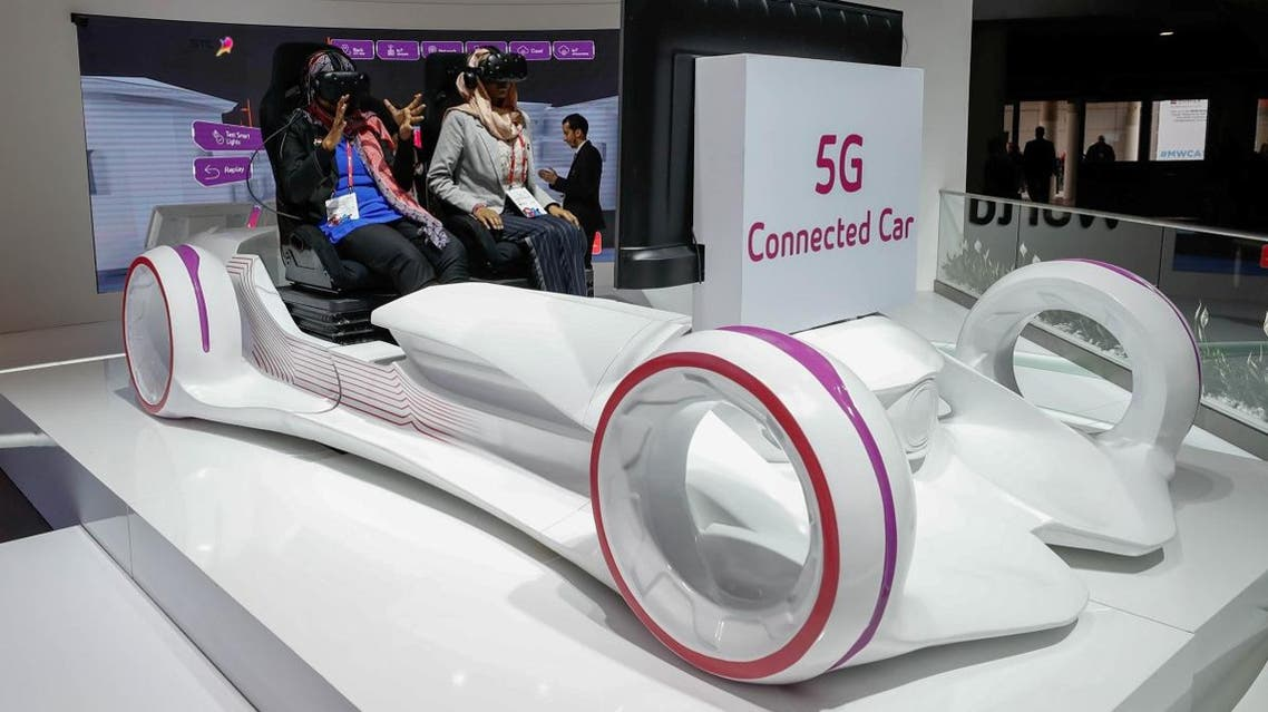 Women sit in a 5G connected car simulator displayed at the Saudi Telecom Company stand during the Mobile World Congress in Barcelona, Spain, February 27, 2018. (Reuters)