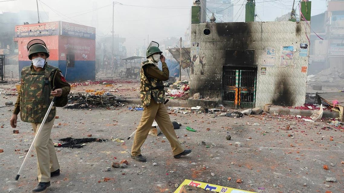 Policemen stand on a vandalised road following clashes between supporters and opponents of a new citizenship law, at Bhajanpura area of New Delhi on February 24, 2020. (AFP)