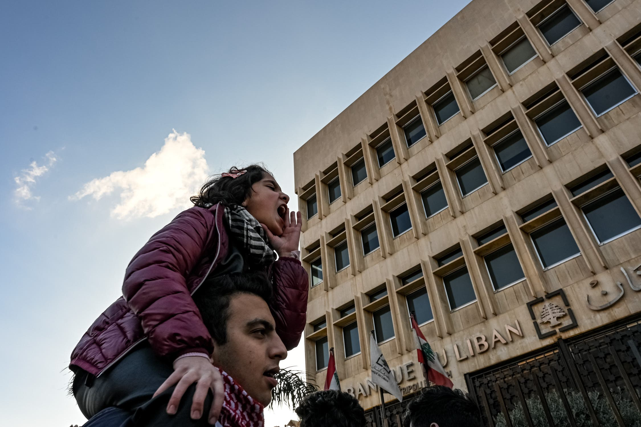 A young girl leads a chant at a protest in front of Tripoli's central bank. (Finbar Anderson)