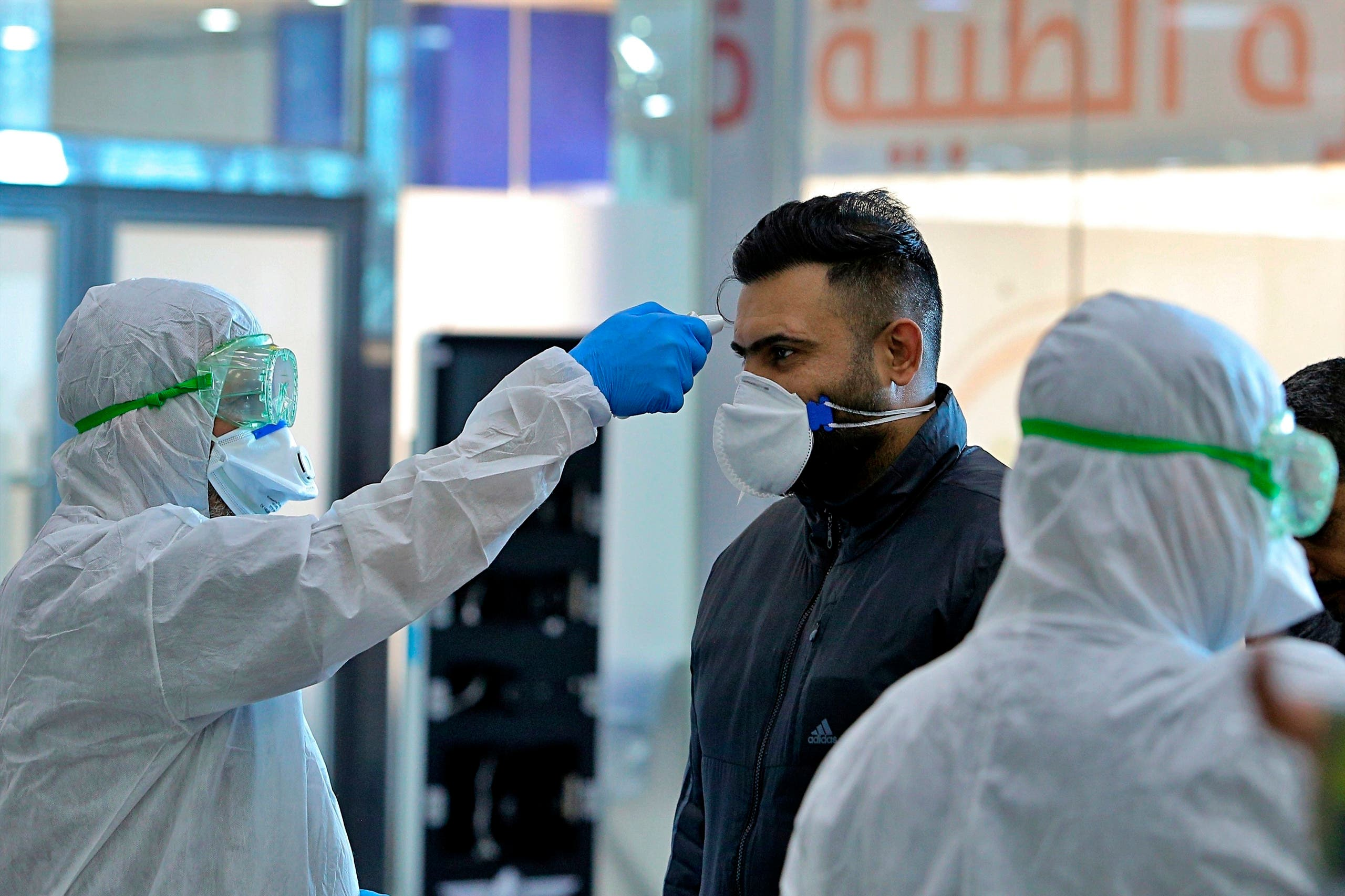 In this Friday, Feb. 21, 2020, file photo, medical staff check passengers arriving from Iran in the airport in Najaf, Iraq. Coronavirus-infected travelers from Iran already have been discovered in Lebanon and Canada. (AP Photo/Anmar Khalil, File)