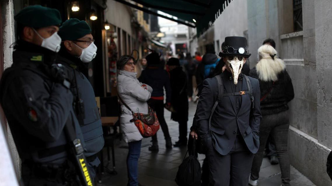 Security personnel wearing protective masks stand next to carnival revelers at Venice Carnival, which the last two days of, as well as Sunday night's festivities, have been cancelled because of an outbreak of coronavirus. (Reuters)