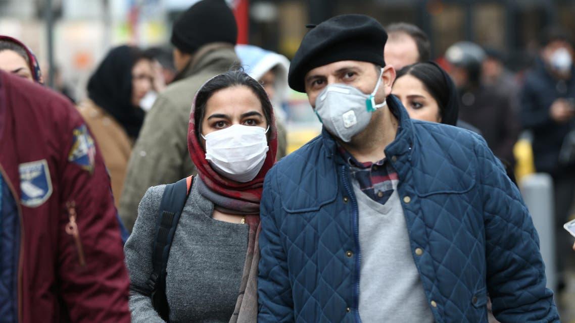Iranian couple wearing protective masks to prevent contracting a coronavirus walk at Grand Bazaar in Tehran, Iran February 20, 2020. WANA (West Asia News Agency)/Nazanin Tabatabaee via REUTERS