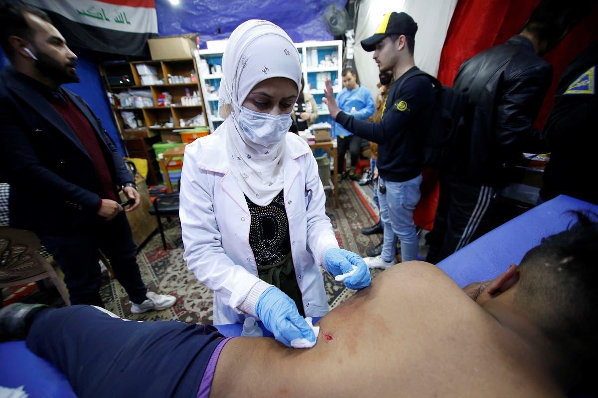 Hannaa Jassem, 24, an Iraqi nurse helps a wounded man in Baghdad, Iraq January 12, 2020. (Reuters)