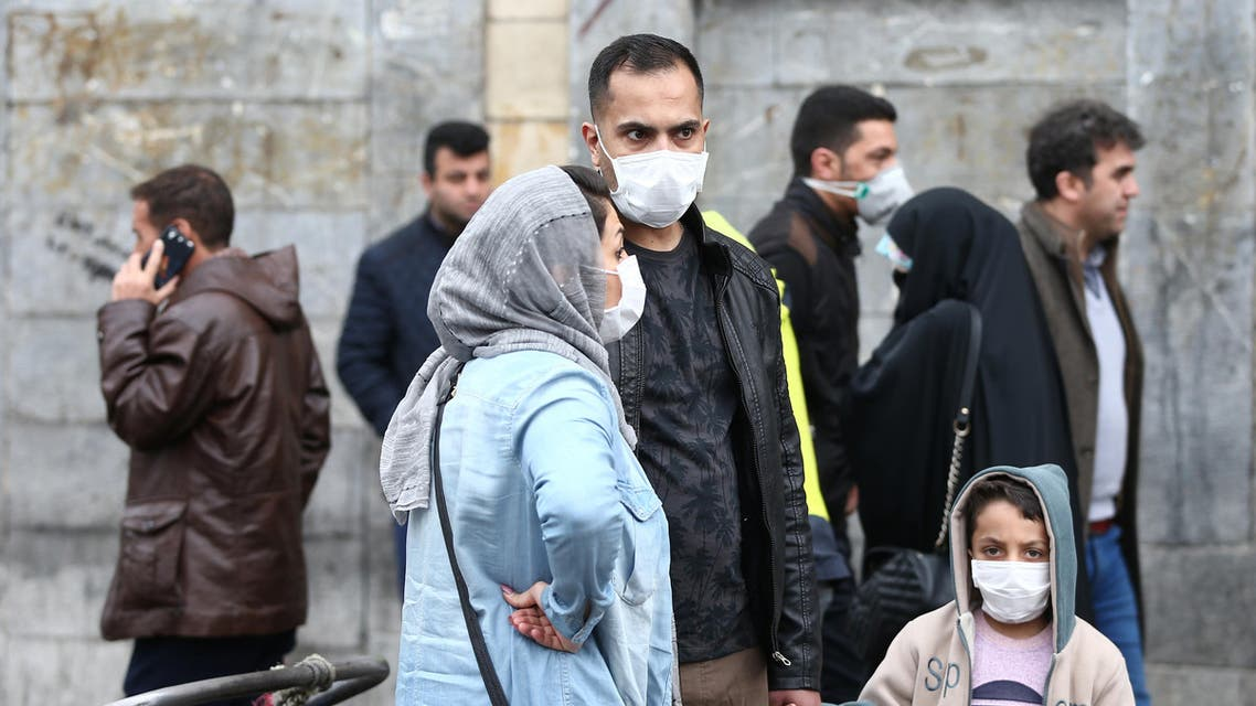 Iranian family wear protective masks to prevent contracting a coronavirus, as they stand at Grand Bazaar in Tehran, Iran. (Reuters)