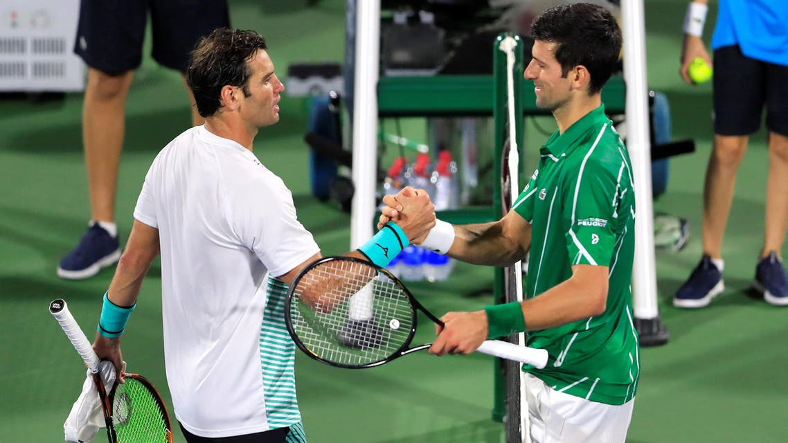 Serbia's Novak Djokovic shakes hands with Tunisia's Malek Jaziri after their match at Dubai Duty Free Tennis Stadium on February 24, 2020.  (Reuters)