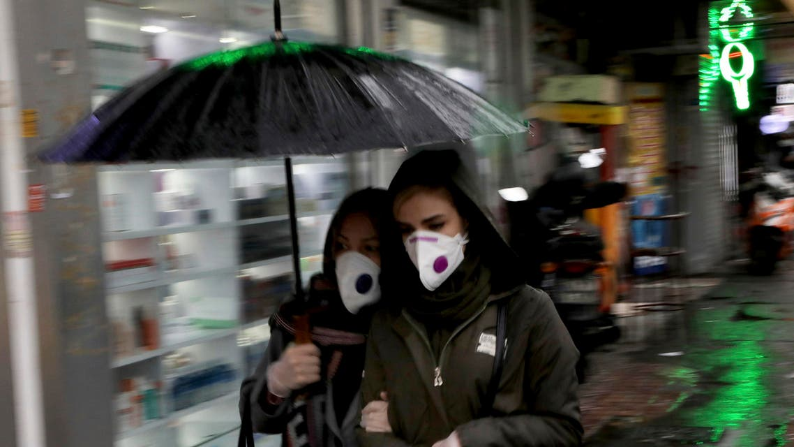 Pedestrians wear masks and gloves to help guard against the coronavirus in downtown Tehran on Feb. 25, 2020. (AP)