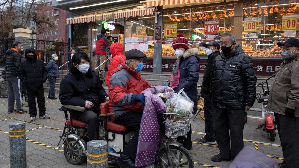 Residents wear masks and line up to enter a supermarket which is controlling the numbers of shoppers in Beijing, China on February 25, 2020. (AP)
