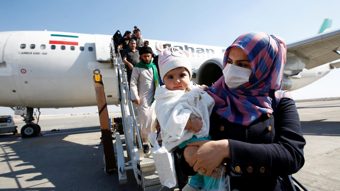 Passengers wearing protective masks disembark from a plane upon their arrival at Najaf airport, amid the new coronavirus outbreak, Iraq. (Reuters)