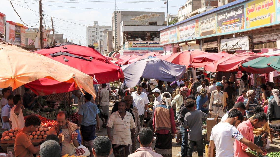 People browse for produce from stalls at a market in the district of Sheikh Othman in Yemen's southern port city of Aden on January 17, 2020.