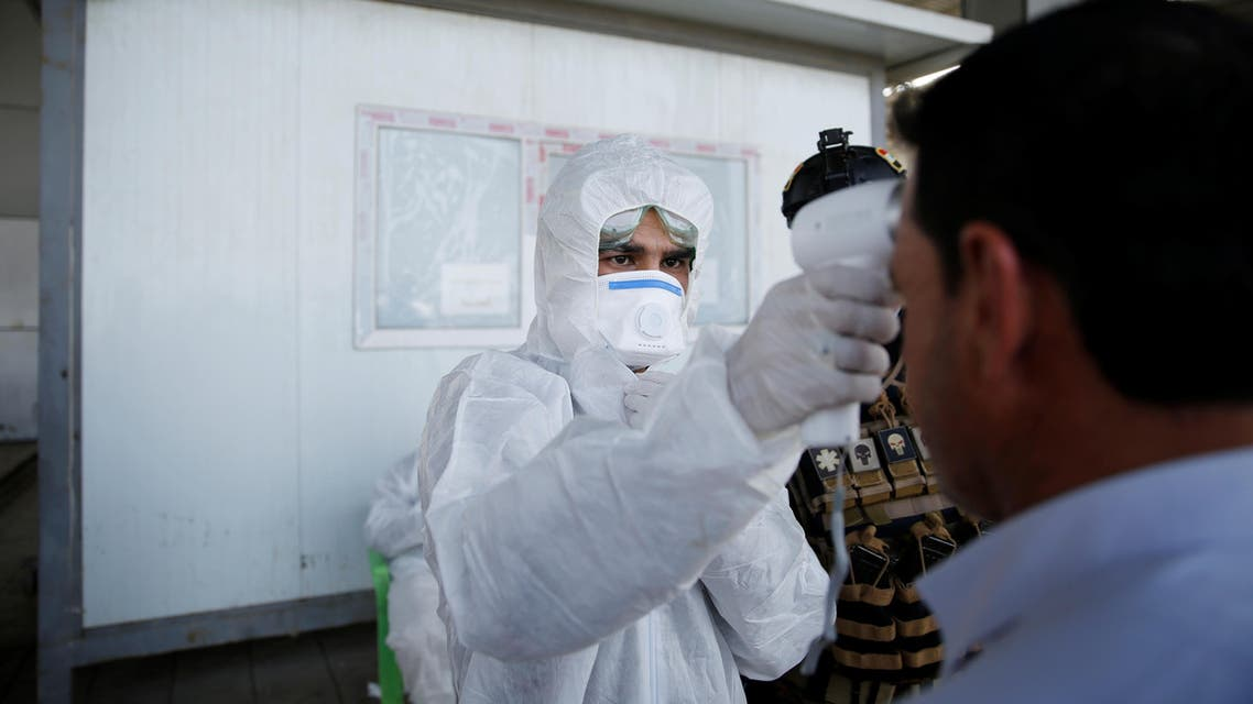 A member of the medical team checks the temperature of an Iraqi man, following the coronavirus outbreak, at the entrance checkpoint of South Mosul, Iraq, February 26, 2020. (Reuters)
