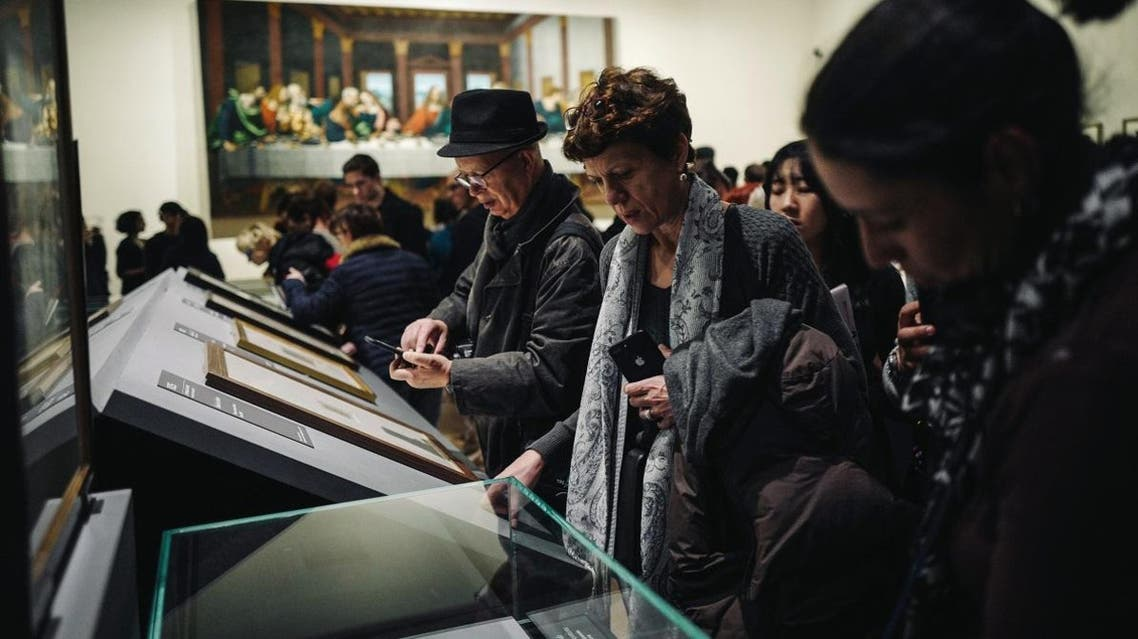 Visitors look at artefacts during the night and free opening of the 'Leonardo da Vinci' exhibition at The Louvre Museum on February 21, 2020 in Paris. (AFP)
