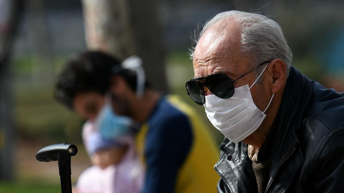 People wearing protective face masks sit outside the AHEPA hospital, where the first confirmed coronavirus case is being treated, in Thessaloniki. (Reuters)