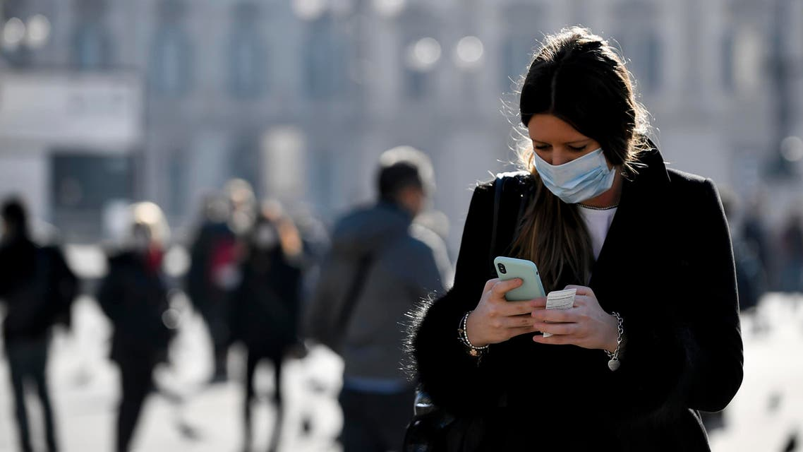 A woman wearing a sanitary mask looks at her phone in Milan on Feb. 24, 2020.  (AP)